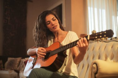 Young beautiful woman sitting on a sofa and playing on a guitar at home.