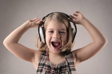 Little girl with headphones listening to music happily.