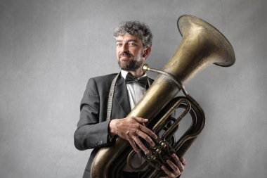 Handsome elegant man with bow-tie and a tuba.