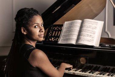 Black woman musician playing piano.
