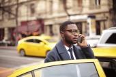 Černé podnikatel taxíkem a mluví na smartphone ve městě