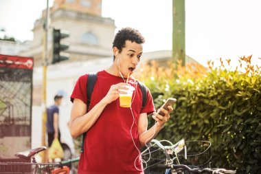 Young man with earphones and a refresher checking surprisingly his smartphone.
