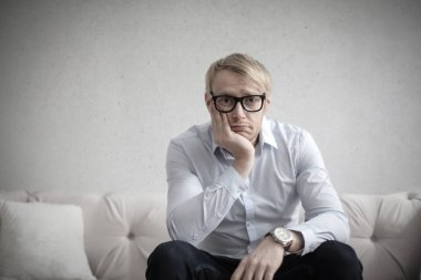 Blond man with glasses thinking desperately on a couch.