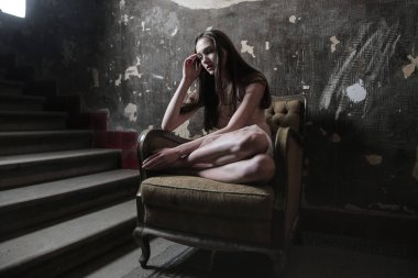 Sad young woman sitting in an armchair and thinking desperately.