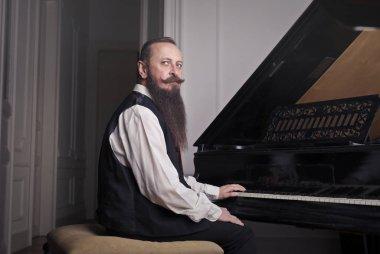 Beared man playing piano