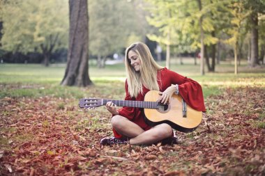 woman playing the guitar in the forest