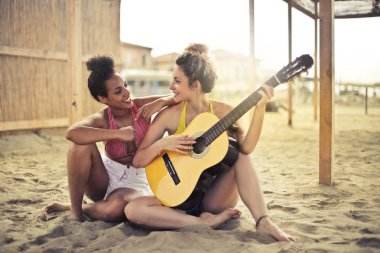 two young woman playing the guitar on the beach