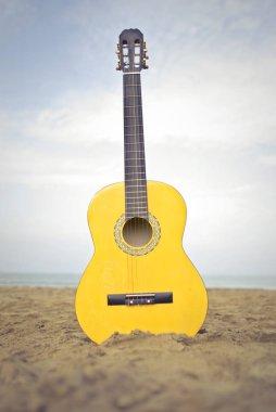 yellow guitar on the beach