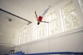 Fényképek Az edzőteremben teljesítő fiatal acrobat