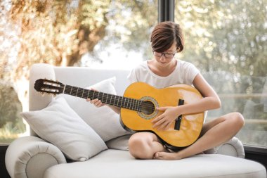 woman with her guitar sitting in a couch