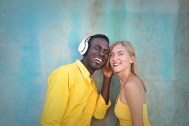 blonde young woman and black handsome man are listening to the music together