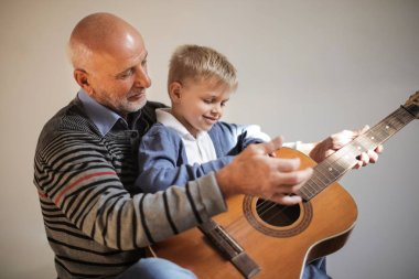 grandfather and his grandson playing the guitar together