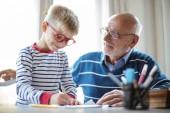 Fotografie kleiner Junge zeichnet, während sein Großvater über ihn wacht
