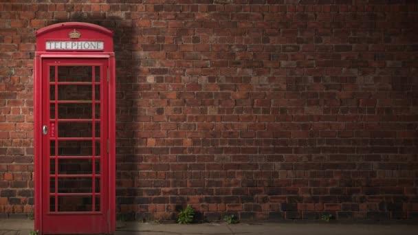 Tradiční britská telefonní budka, jak vrhá svůj stín přes červenou cihlovou zeď během dne