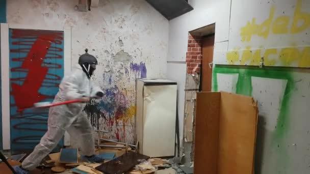 Zralý muž ničí starou lednici kladivem v troskách
