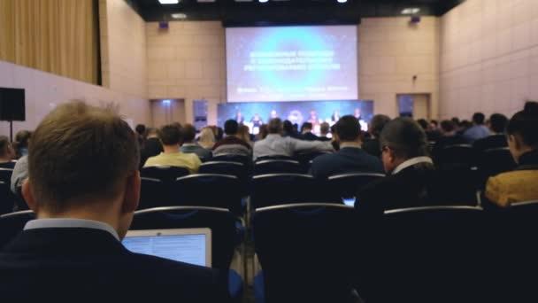 Publikum poslouchá přednášející na konferenci