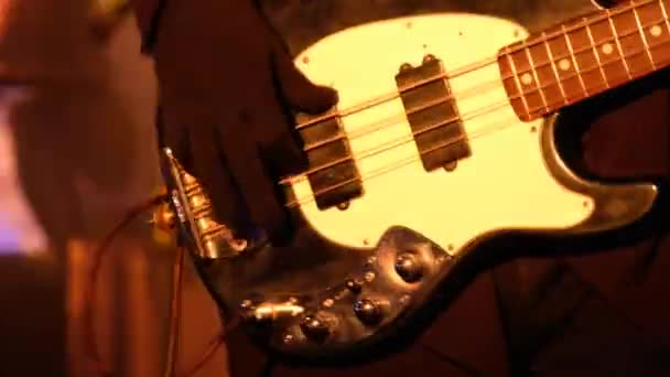 Kytarista hraje basovou kytaru na live koncert