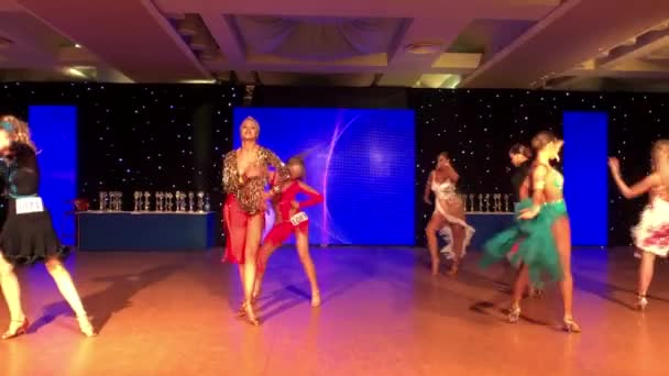 Girls wearing colourful dresses take part in dance competitions