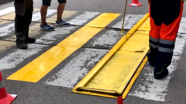 Road workers put paint on a crosswalk sign
