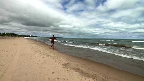 Fiatal, boldog nő fut a strandon