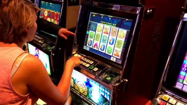 Woman playing slot machine in casino ⬇ Video by © toxawww Stock Footage  #236945146