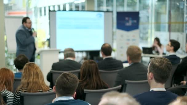 Zuhörer lauschen dem Vortragenden auf der Konferenz