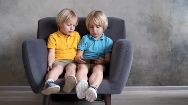Brothers are watching or playing or learning something in a smartphone