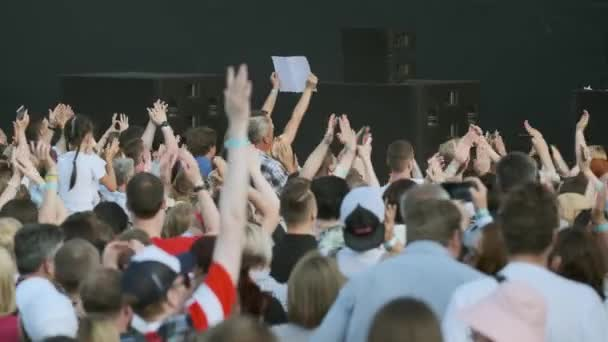 Crowd of fans cheering at open-air music festival