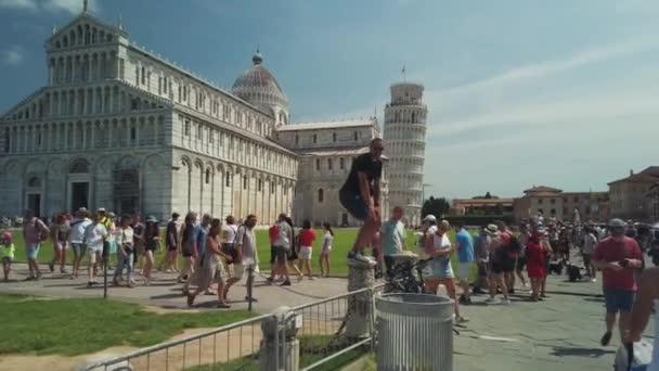 Turisté navštěvující slavnou nakláněnou věž ve dne