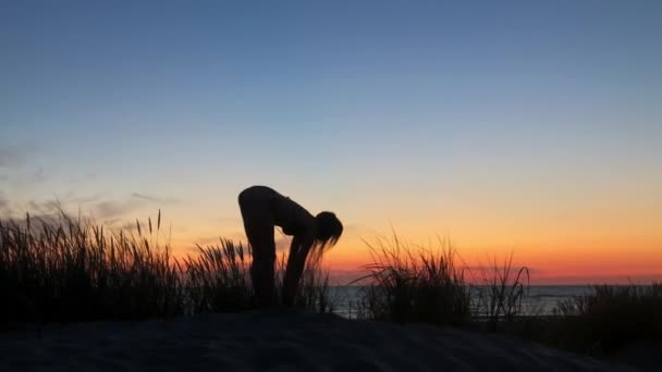 Unrecognizable woman doing yoga on seashore in evening