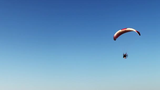 Anonymous person flying on paraglider in sky