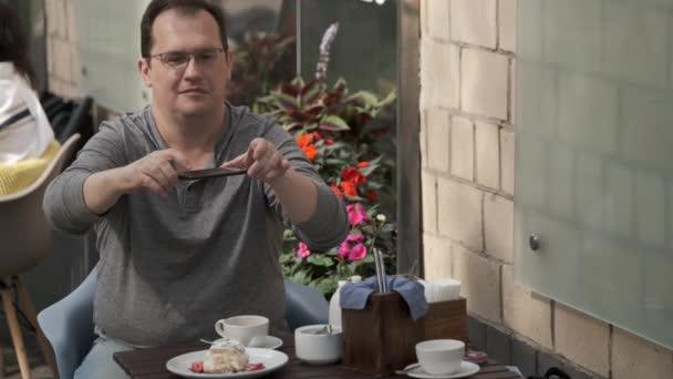 Man taking photo of dessert in cafe