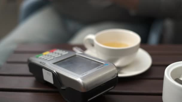 Crop man paying for order in cafe with smartphone