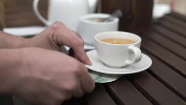 Crop male customer leaving tips in cafe