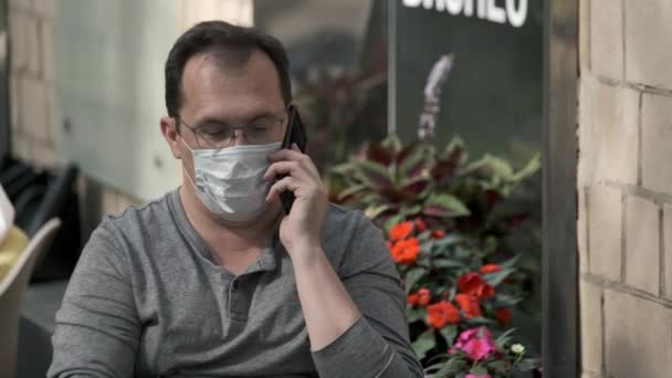 Man in protective mask talking on cellphone in city