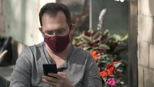 Man using smartphone in summer cafe