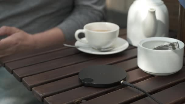 Crop man using wireless charger in outdoors cafe