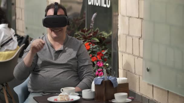 Man using VR glasses in outdoors cafe