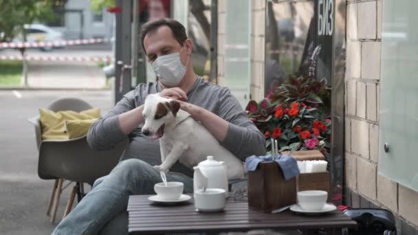 Man in mask caressing dog in street cafe