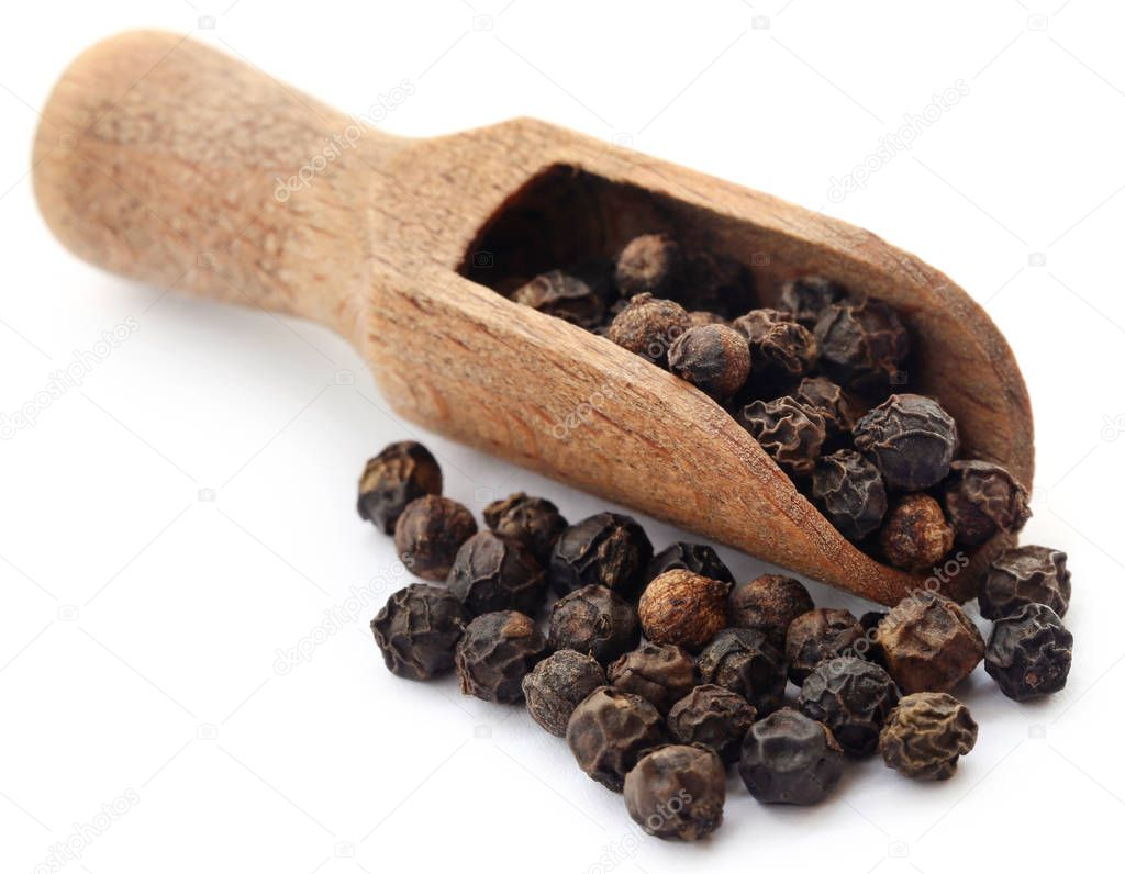 Black peppers on wooden scoop over white background