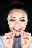 Fotografia Concetto di stomatologia, la testa e le spalle della donna con denti forti e bianchi, guardando la macchina fotografica e sorridente, dente falso della holding, protesi. Giovane donna al dentista, ortodonzia Invisalign