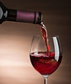 Red wine pouring into wine glass, close-up - Image