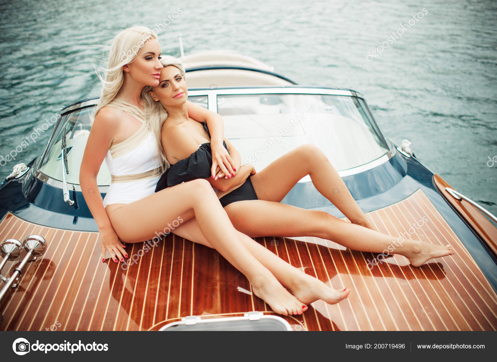 Two pretty blonde girls are wearing sexy fashion swimsuit doing summer trip  on a yacht — Stock Photo © _chupacabra_ #200719496