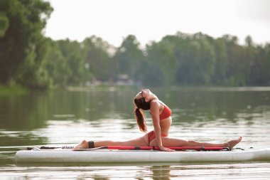 Young pretty fitness girl in swimwear is doing yoga on the SUP in the middle of the lake with a green forest in the background.