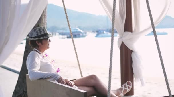 Happy woman in aged in hat and sunglasses resting on a wooden swing on a tropical beach during summer vacation. slow motion. 3840x2160