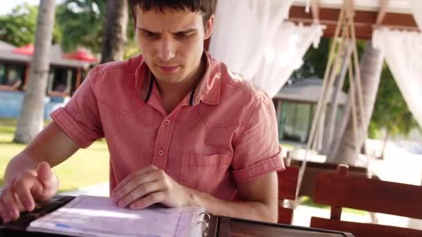 Schöner junger Mann sitzt in einem Café am Strand Schriftrollen durch das Menü, eine Wahl zu treffen will. 3840 x 2160