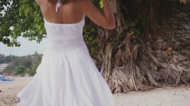 Young brunette woman with long hair in white drees and hat looks back beckoning for herself on tropical beach. slow motion. 3840x2160