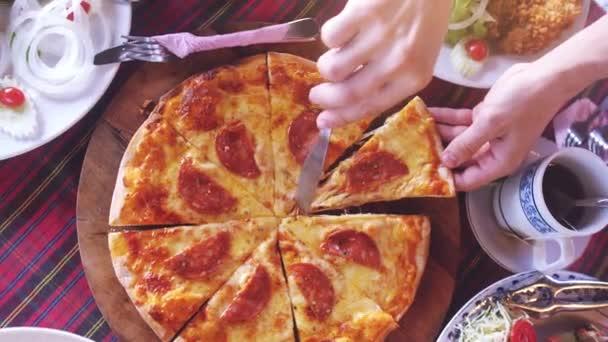 Pohled shora s plátky Pizza se salámem z dřevěné desky. Zpomalený pohyb. 3840 x 2160