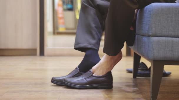 Podnikatel klade na hnědé nové módní boty a ponožky. Zpomalený pohyb. 3840 x 2160