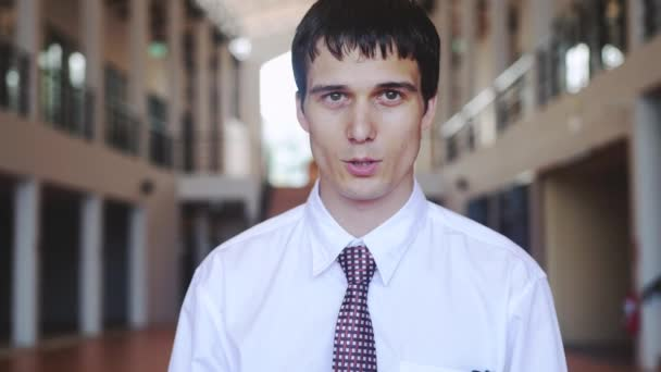 Portrait of successful happy handsome businessman talking to the camera against the backdrop of a business center building. slow motion. 3840x2160.